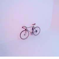 Pink bicycle in white room.