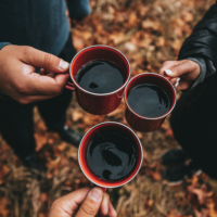 Three people outside each holding a cup of coffee.