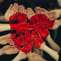 Many hands together, painted with a heart.
